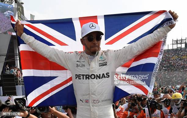 TOPSHOT Mercedes' British driver Lewis Hamilton celebrates after winning his fourth Formula One world title despite finishing the Mexican Grand Prix...