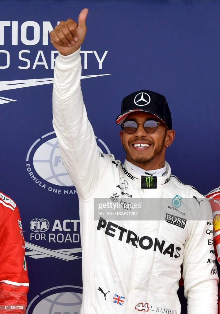 Mercedes' British driver Lewis Hamilton celebrates after winning the pole position after the qualifying session at the Silverstone motor racing circuit in Silverstone, central England on July 15, 2017 ahead of the British Formula One Grand Prix. / AFP PHOTO / Andrej ISAKOVIC
