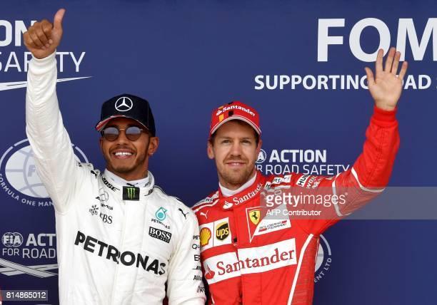 Mercedes' British driver Lewis Hamilton celebrates after winning the pole position next to third placed Ferrari's German driver Sebastian Vettel...
