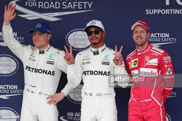 TOPSHOT Mercedes' British driver Lewis Hamilton celebrates his pole position with second placed Mercedes' Finnish driver Valtteri Bottas and third...