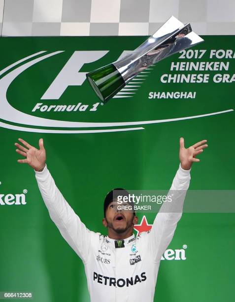 TOPSHOT Mercedes' British driver Lewis Hamilton celebrates on the podium after winning the Formula One Chinese Grand Prix in Shanghai on April 9 2017...