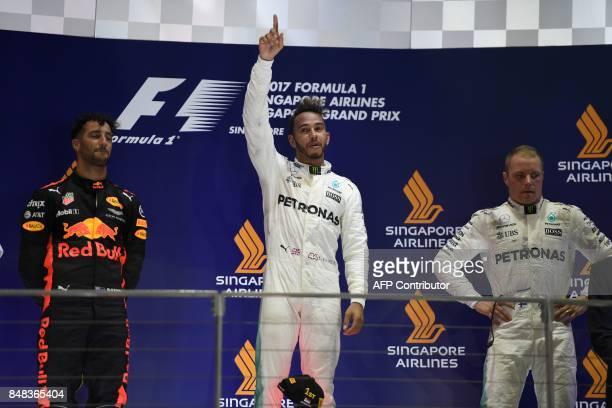 Mercedes' British driver Lewis Hamilton celebrates on the podium with secondplaced Red Bull's Australian driver Daniel Ricciardo and thirdplaced...