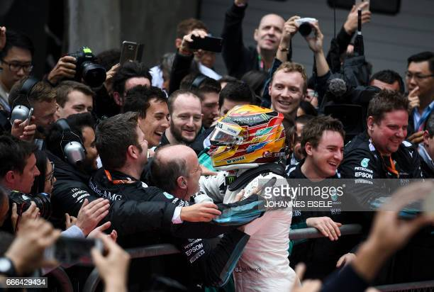 Mercedes' British driver Lewis Hamilton celebrates with his team after winning the Formula One Chinese Grand Prix in Shanghai on April 9 2017 / AFP...
