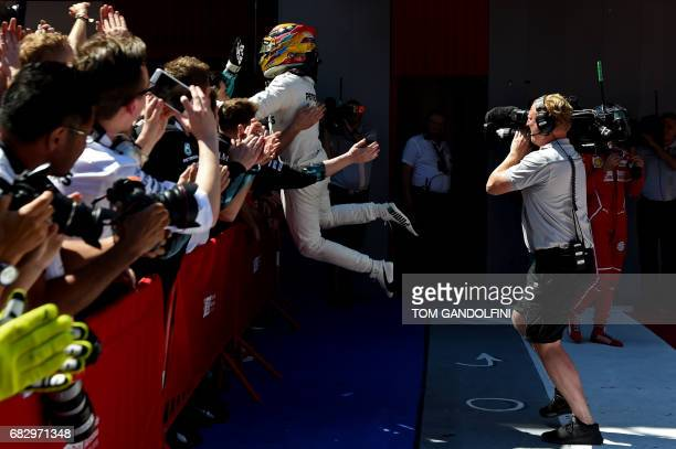 Mercedes' British driver Lewis Hamilton celebrates with team members in the parc ferme after winning the Spanish Formula One Grand Prix on May 14...
