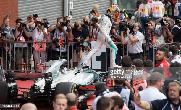 TOPSHOT Mercedes' British driver Lewis Hamilton climbs out of his car as he celebrates after victory in the Belgian Formula One Grand Prix at the...