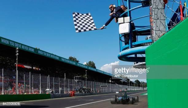Mercedes' British driver Lewis Hamilton crosses the finish line to win the Italian Formula One Grand Prix at the Autodromo Nazionale circuit in Monza...