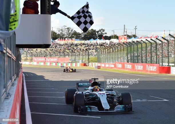 TOPSHOT Mercedes' British driver Lewis Hamilton crosses the finish line to win the Formula One Japanese Grand Prix at Suzuka on October 8 2017 / AFP...
