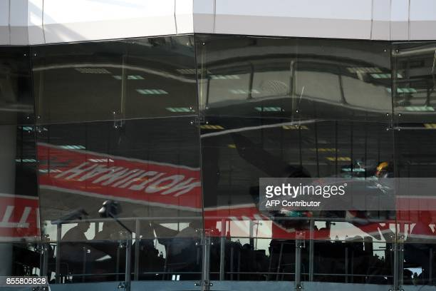 Mercedes' British driver Lewis Hamilton is reflected in the glass windows as he drives into the pitlane during the qualifying session of the Formula...