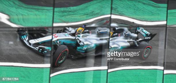 TOPSHOT Mercedes' British driver Lewis Hamilton is reflected on windows as he powers his car during the Brazilian Formula One Grand Prix third...