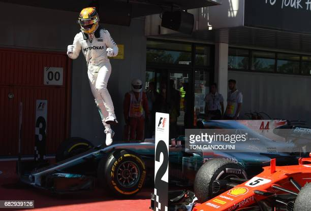 Mercedes' British driver Lewis Hamilton jumps from his car as he celebrates winning at the Circuit de Catalunya on May 14 2017 in Montmelo on the...