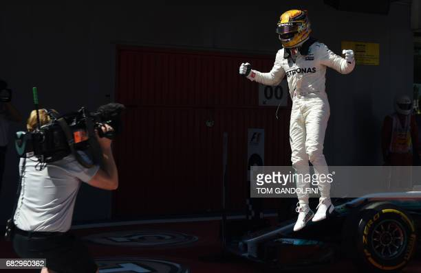 TOPSHOT Mercedes' British driver Lewis Hamilton jumps from his car as he celebrates winning at the Circuit de Catalunya on May 14 2017 in Montmelo on...