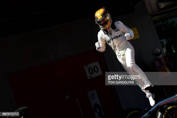 Mercedes' British driver Lewis Hamilton jumps off his car in the parc ferme after winning the Spanish Formula One Grand Prix on May 14 2017 at the...
