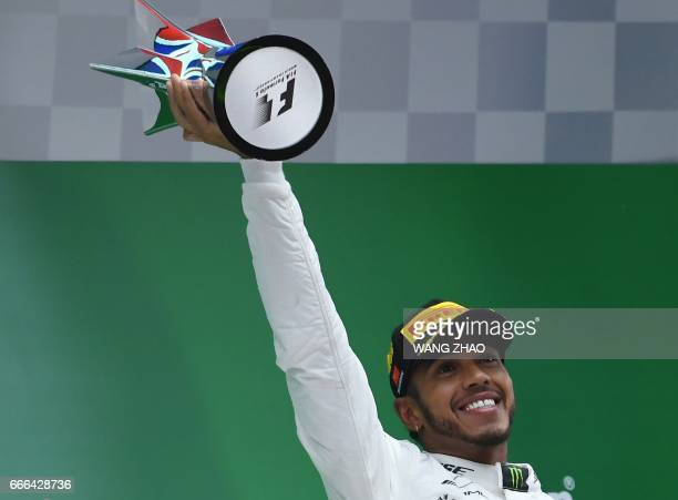 Mercedes' British driver Lewis Hamilton raises the trophy after winning the Formula One Chinese Grand Prix as he celebrates on the podium in Shanghai...