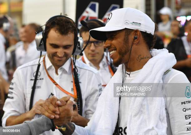 Mercedes' British driver Lewis Hamilton shakes hands as he prepares on the starting grid ahead of the Bahrain Formula One Grand Prix at the Sakhir...