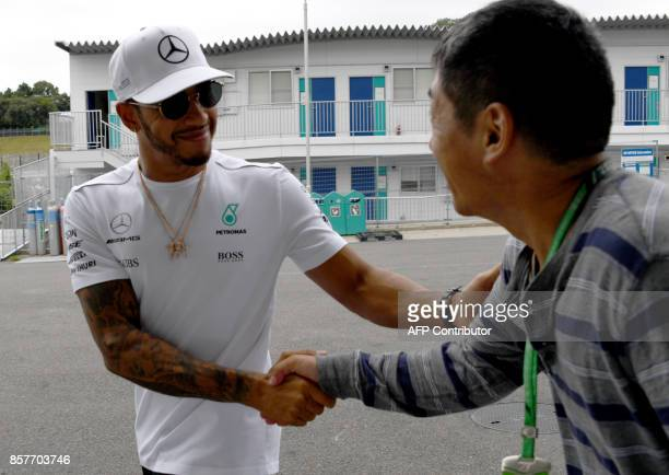 Mercedes' British driver Lewis Hamilton shakes hands with a fan in the paddock one day before start of the practice sessions for the Formula One...