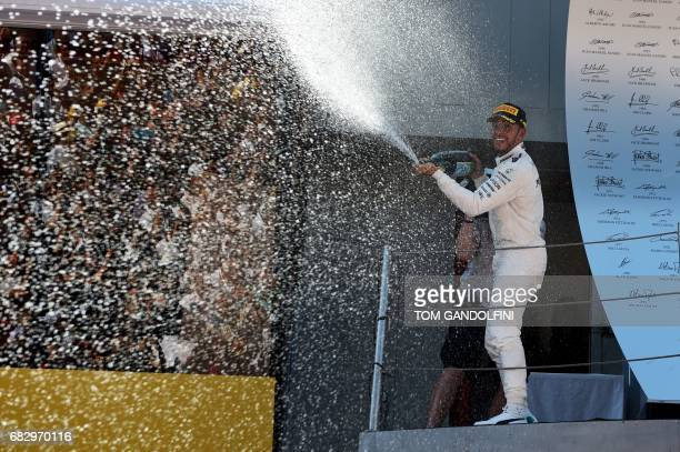 Mercedes' British driver Lewis Hamilton sprays Cava as he celebrates on the podium after winning the Spanish Formula One Grand Prix on May 14 2017 at...
