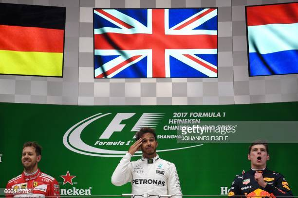 Mercedes' British driver Lewis Hamilton stands on the podium with secondplaced Ferrari's German driver Sebastian Vettel and thirdplaced Red Bull's...