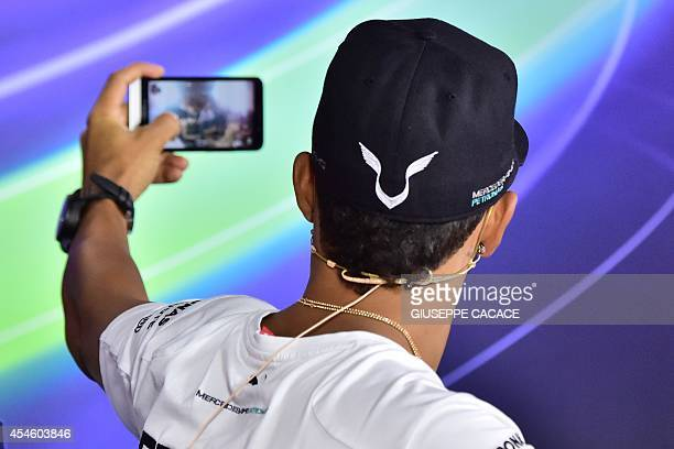 Mercedes' British driver Lewis Hamilton takes a selfie during a press conference at the Autodromo Nazionale circuit in Monza on September 4 2014...