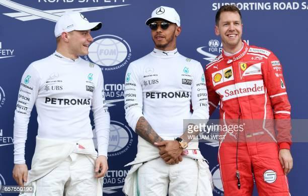 Mercedes' British driver Lewis Hamilton teammate Mercedes' Finnish driver Valtteri Bottas and Ferrari's German driver Sebastian Vettel chat after the...