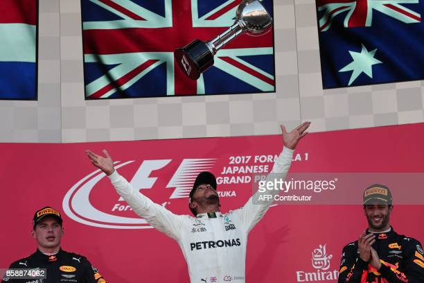 TOPSHOT Mercedes' British driver Lewis Hamilton throws his winner's trophy as second placed Red Bull's Dutch driver Max Verstappen and Red Bull's...