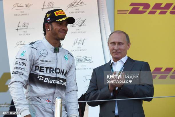 Mercedes' British driver Lewis Hamilton walks to the podium by Russian President Vladimir Putin after winning the inaugural Russian Formula 1 Grand...