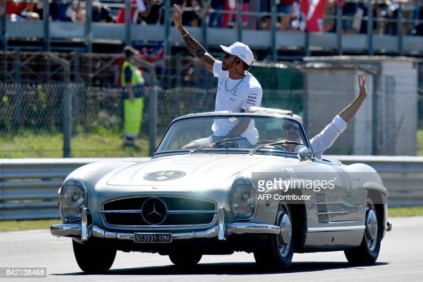Mercedes' British driver Lewis Hamilton waves from a historical Mercedes car during a car parade ahead of the Italian Formula One Grand Prix at the...