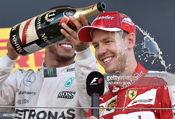 Mercedes driver Lewis Hamilton of Britain celebrates his victory on the podium as he pours champagne over thirdplaced Ferrari's German driver...