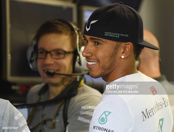 Mercedes driver Lewis Hamilton of Britain chats with his team officers prior to the first practice session of the Formula One Singapore Grand Prix at...