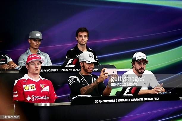Mercedes driver Lewis Hamilton of Britain records video footage using his smartphone during a joint press conference with Scuderia Ferrari's Finnish...