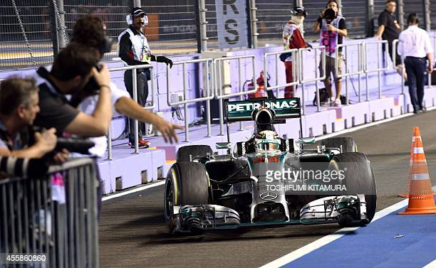 Mercedes driver Lewis Hamilton of Britain returns to the parc ferme after winning the Formula One Singapore Grand Prix in Singapore on September 21...