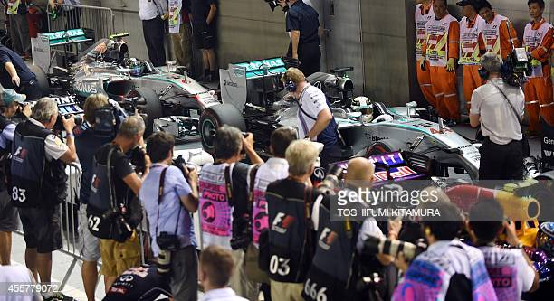 Mercedes driver Lewis Hamilton of Britain returns to the pit with his teammate Nico Rosberg of Germany after Hamilton clinched pole position for the...