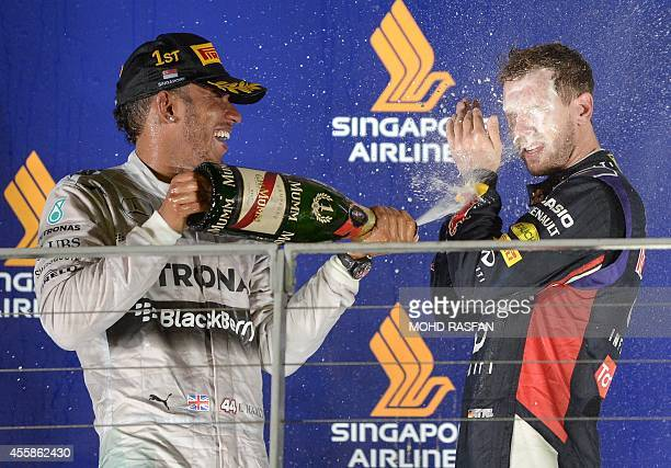 Mercedes driver Lewis Hamilton of Britain sprays a bottle of champagne over second placed Red Bull Racing driver Sebastian Vettel of Germany on the...