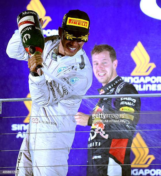 Mercedes driver Lewis Hamilton of Britain sprays the bottle of champagne while second placer Red Bull Racing driver Sebastian Vettel of Germany...