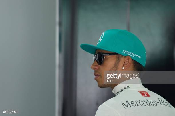 Mercedes driver Lewis Hamilton of Britain walks inside his team garage during the second practice session ahead of the Formula One Malaysian Grand...