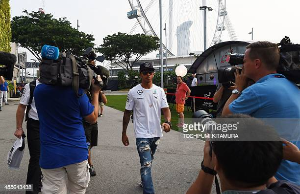 Mercedes driver Lewis Hamilton of Britain walks on the paddock upon his arrival at the Marina Bay Street Circuit for the Formula One Singapore Grand...