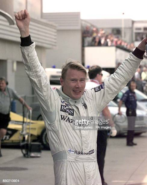 Mercedes driver Mikka Hakkinen celebrates gaining pole position for the British Grand Prix after finishing ahead of rival Michael Schumacher at...