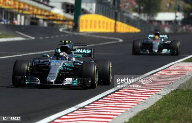 Mercedes' Finnish driver Valtteri Bottas and Mercedes' British driver Lewis Hamilton race at the Hungaroring circuit in Budapest on July 30 during...