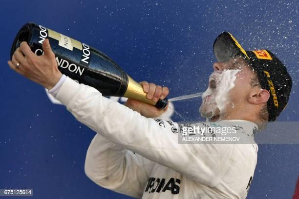 TOPSHOT Mercedes' Finnish driver Valtteri Bottas celebrates on the podium after winning the Formula One Russian Grand Prix at the Sochi Autodrom...