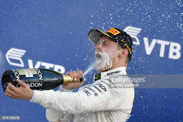Mercedes' Finnish driver Valtteri Bottas celebrates on the podium after winning the Formula One Russian Grand Prix at the Sochi Autodrom circuit in...