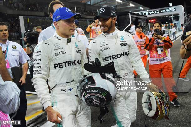 Mercedes' Finnish driver Valtteri Bottas celebrates with his teammate British driver Lewis Hamilton after taking the pole position at the end of the...