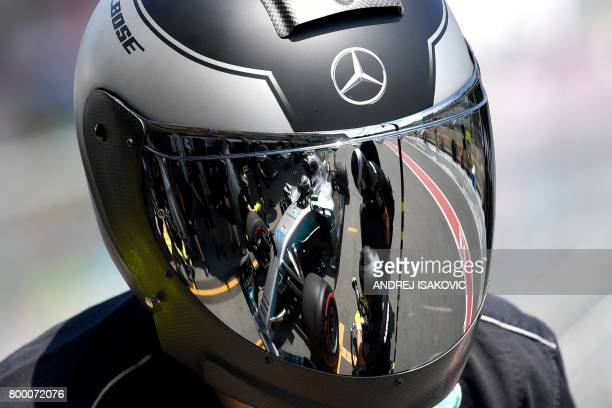 TOPSHOT Mercedes' Finnish driver Valtteri Bottas is seen reflected in the helmet of a mechanic during the first practice session of the Formula One...