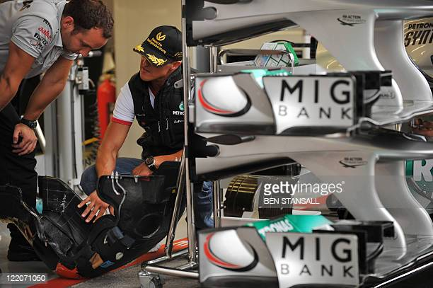 Mercedes' German driver Michael Schumacher speaks to a technician in the pits on August 25 2011 in Spa ahead of the Belgium Formula One Grand Prix...