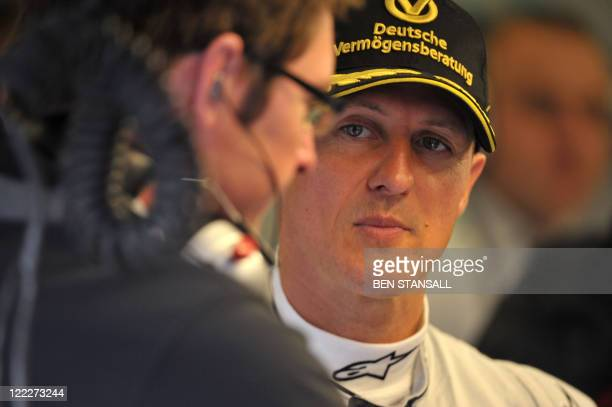 Mercedes' German driver Michael Schumacher talks to team mates in the pits at the SpaFrancorchamps circuit on August 27 2011 in Spa during the third...