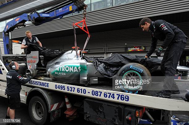 Mercedes' German driver Michael Schumacher's car is hoisted off a truck after crashing in the pits after crashing at the SpaFrancorchamps circuit on...