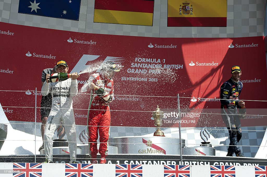 Mercedes' German driver Nico Rosberg (L) celebrates his victory by spraying champagne on the podium with second place, Red Bull's Australian driver Mark Webber (R) and third place, Ferrari's Spanish driver Fernando Alonso (C) at the Silverstone circuit in Silverstone on June 30, 2013 after the British Formula One Grand Prix.