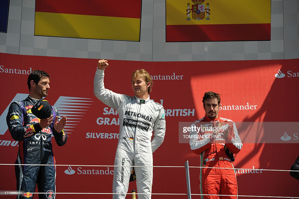 Mercedes' German driver Nico Rosberg (C) celebrates his victory on the podium beside second place, Red Bull's Australian driver Mark Webber (L) and third place, Ferrari's Spanish driver Fernando Alonso (R) at the Silverstone circuit in Silverstone on June 30, 2013 after the British Formula One Grand Prix. AFP PHOTO / TOM GANDOLFINI