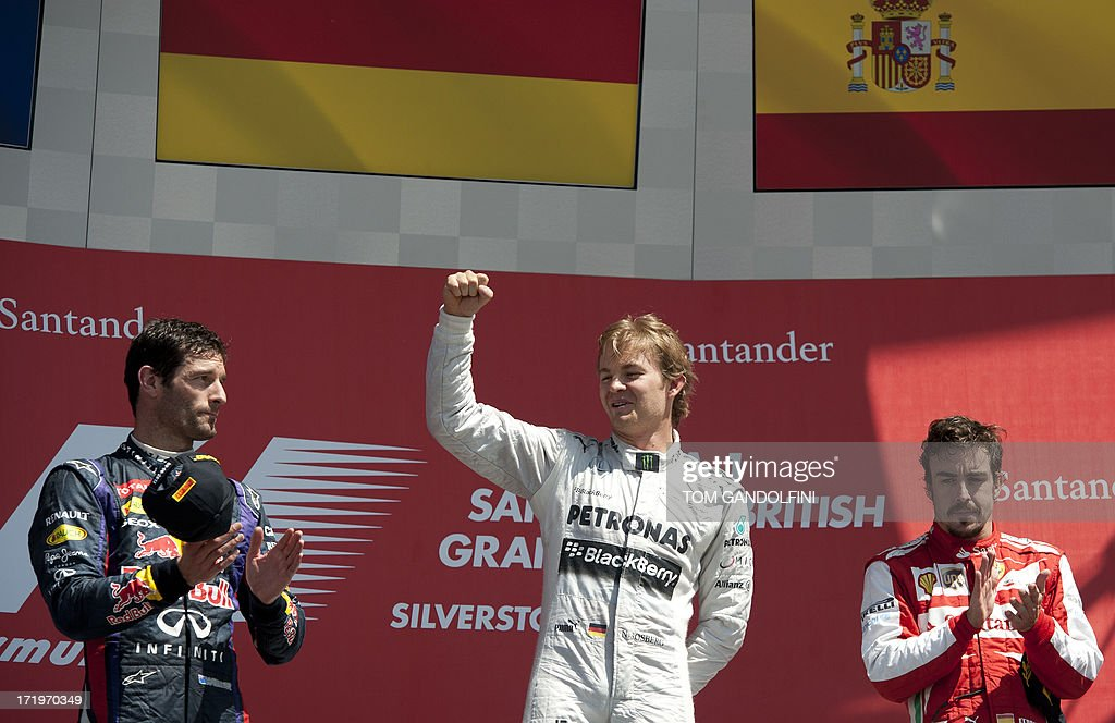 Mercedes' German driver Nico Rosberg (C) celebrates his victory on the podium beside second place, Red Bull's Australian driver Mark Webber (L) and third place, Ferrari's Spanish driver Fernando Alonso (R) at the Silverstone circuit in Silverstone on June 30, 2013 after the British Formula One Grand Prix.