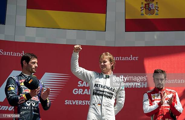 Mercedes' German driver Nico Rosberg celebrates his victory on the podium beside second place Red Bull's Australian driver Mark Webber and third...
