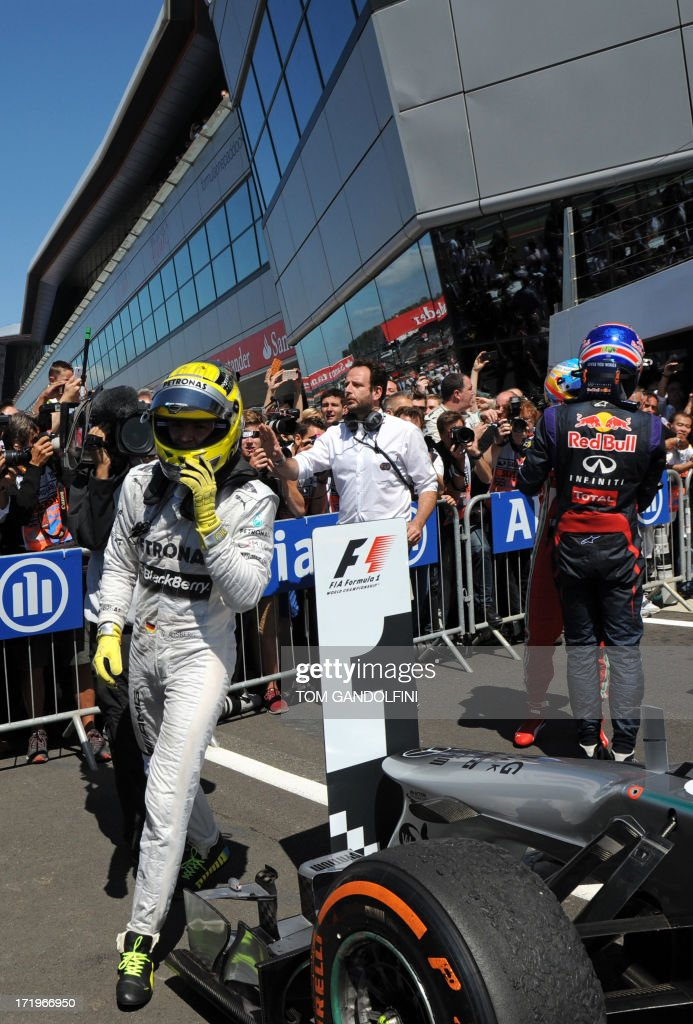 Mercedes' German driver Nico Rosberg (L) celebrates in the parc ferme near second place driver, Red Bull Racing's Australian driver Mark Webber (R) at the Silverstone circuit in Silverstone on June 30, 2013 after the British Formula One Grand Prix. AFP PHOTO / TOM GANDOLFINI