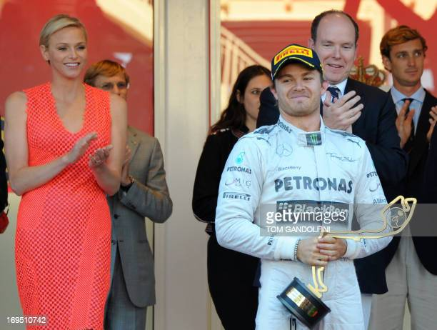 Mercedes' German driver Nico Rosberg celebrates winning as Prince Albert of Monaco and Princess Charlene clap at the Circuit de Monaco in Monte Carlo...